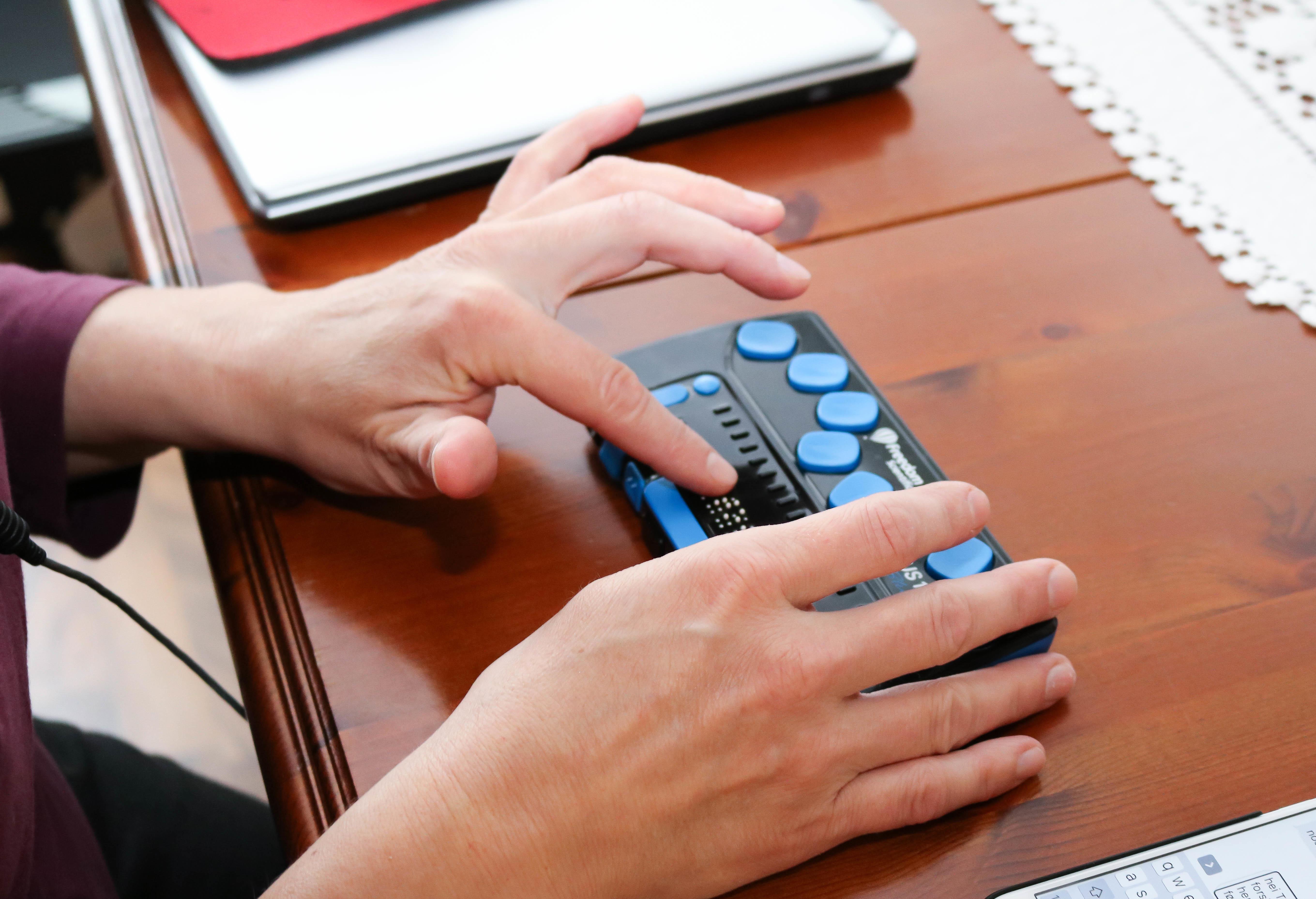 Hender som taster på en leselist med blå knapper.