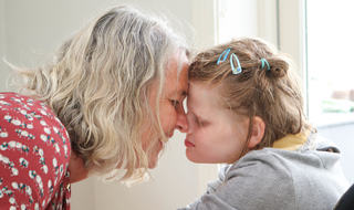 Mor og datter helt tett, panne mot panne. De smiler, datter har øynene igjen.