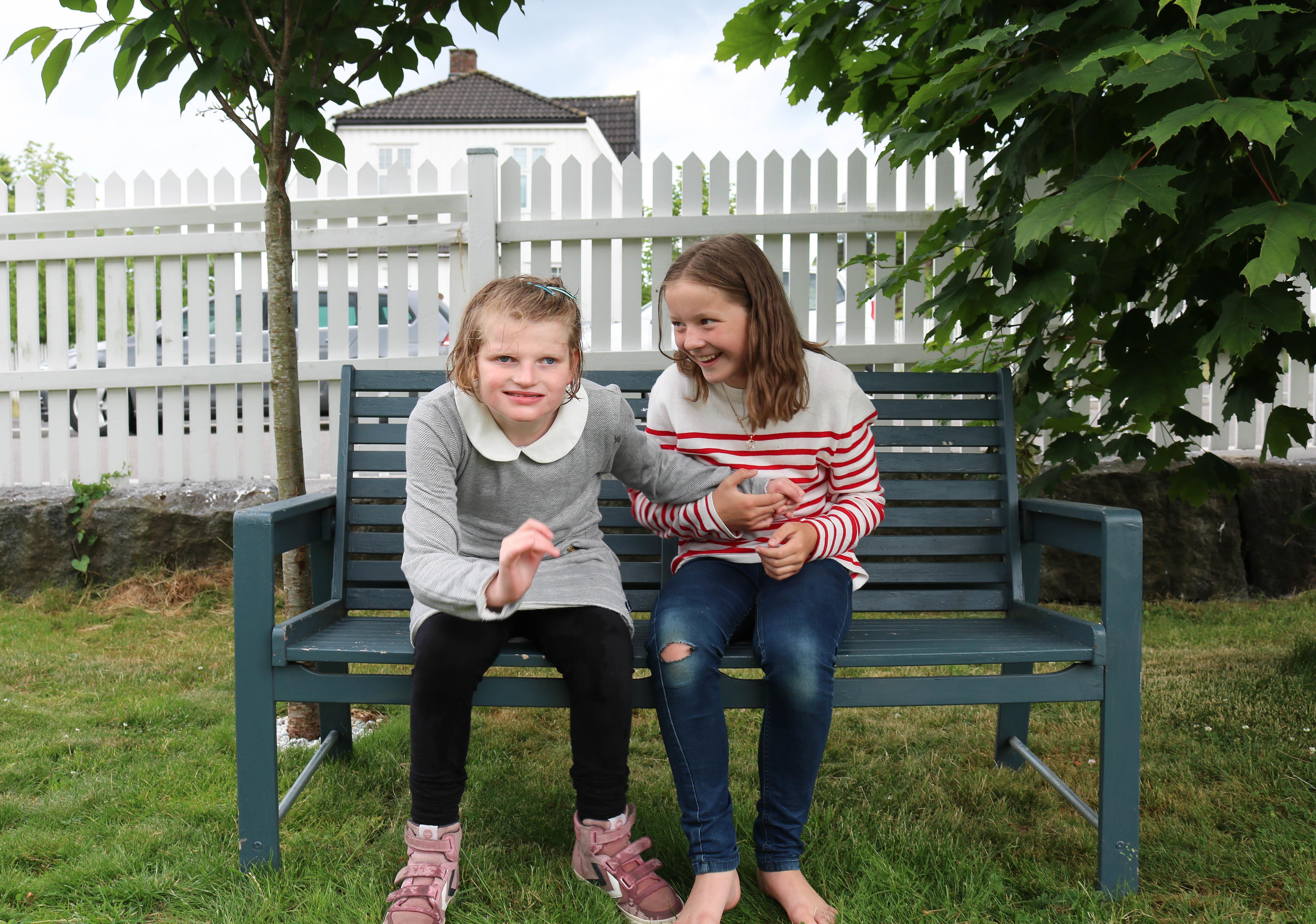 To søstre på en benk i en sommerhage. De smiler begge to, hun til venstre er i ferd med å reise seg.