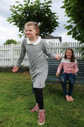 To søstre i en sommerhage. Ei har rød og hvit-stripete genser og sitter på en benk, mens den andre går fra benken har på seg grå kjole.