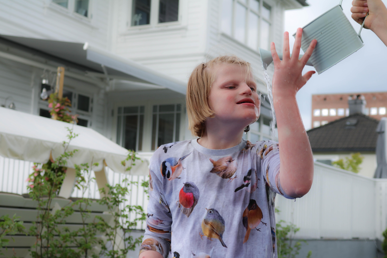 Jente står foran hvit villa, hun holder venstrehånden opp mot en vannkanne. Det renner vann nedover armen hennes.