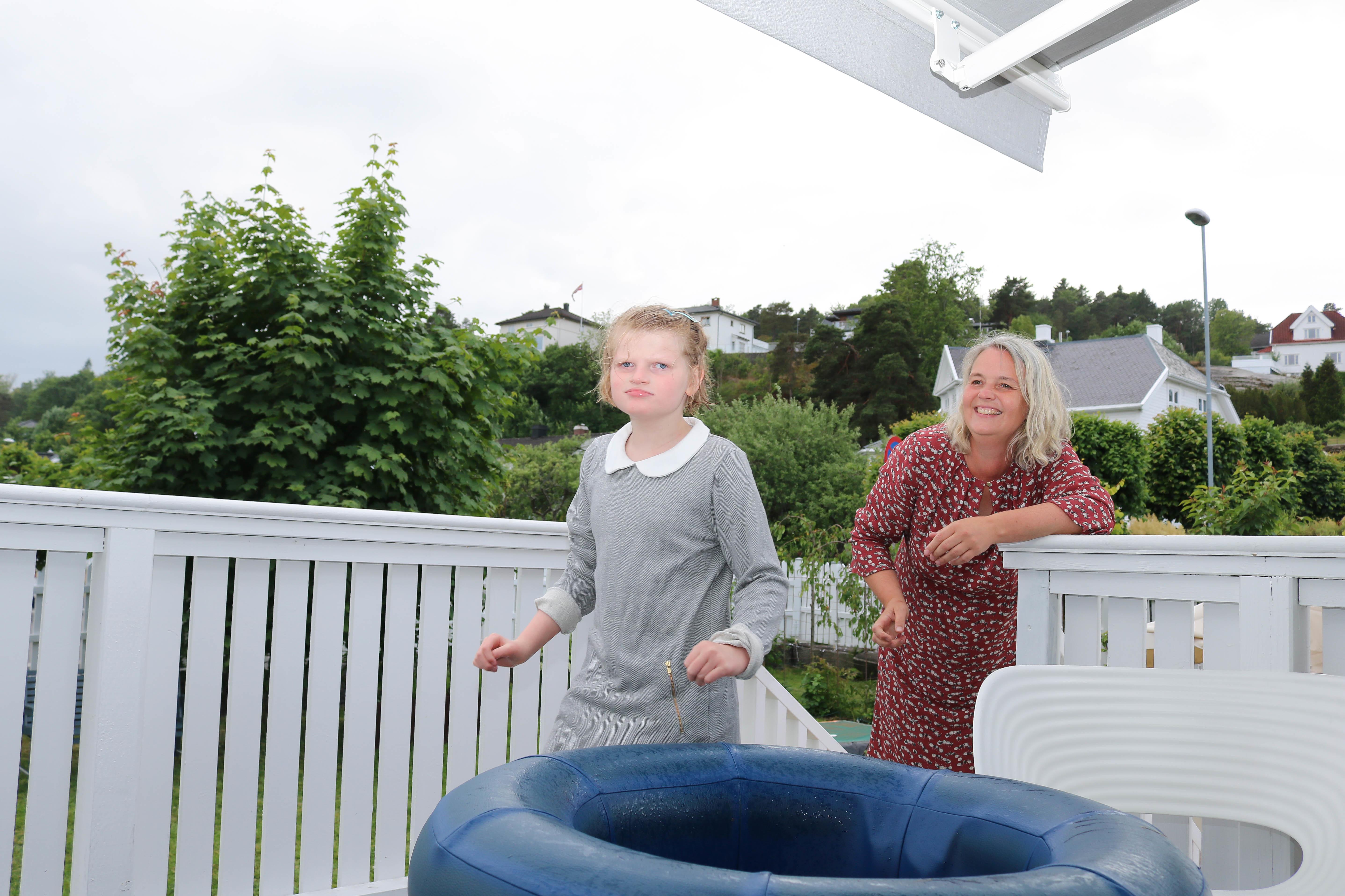 Mor og datter på hvitmalt terrasse. Datter nærmest ved en blå badering.