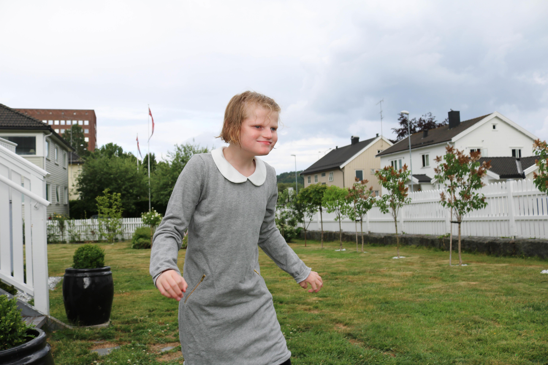 Jente i grå kjole går på plenen i en hage med flere hvite hus i bakgrunnen.