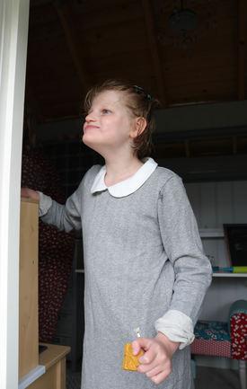 Jente i grå kjole står i en døråpning og ser oppover til venstre.