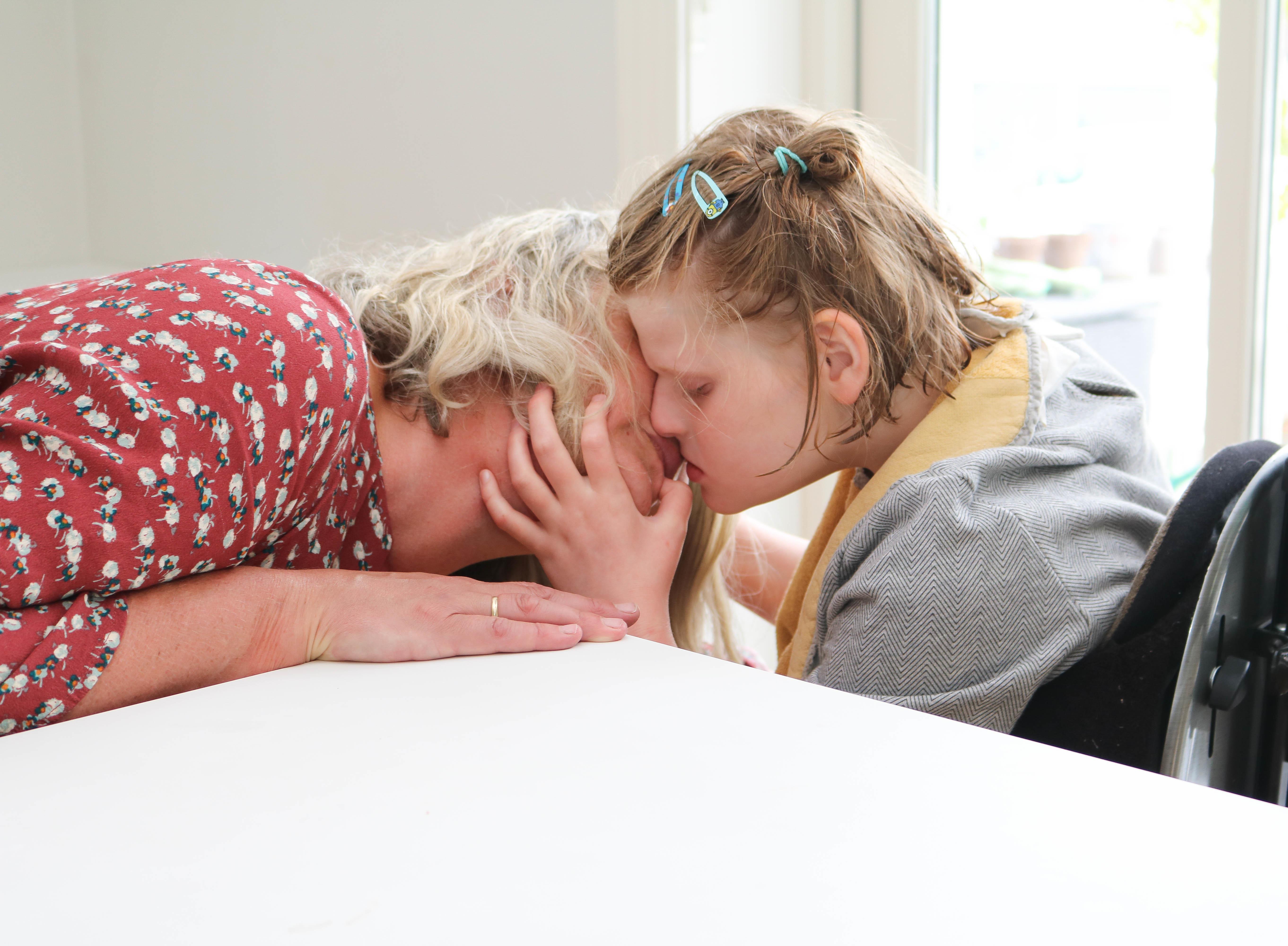 Mor og datter helt tett, hodet mot hodet. Datter klemmer sin venstre hånd rundt morens hake, hals og kinn.