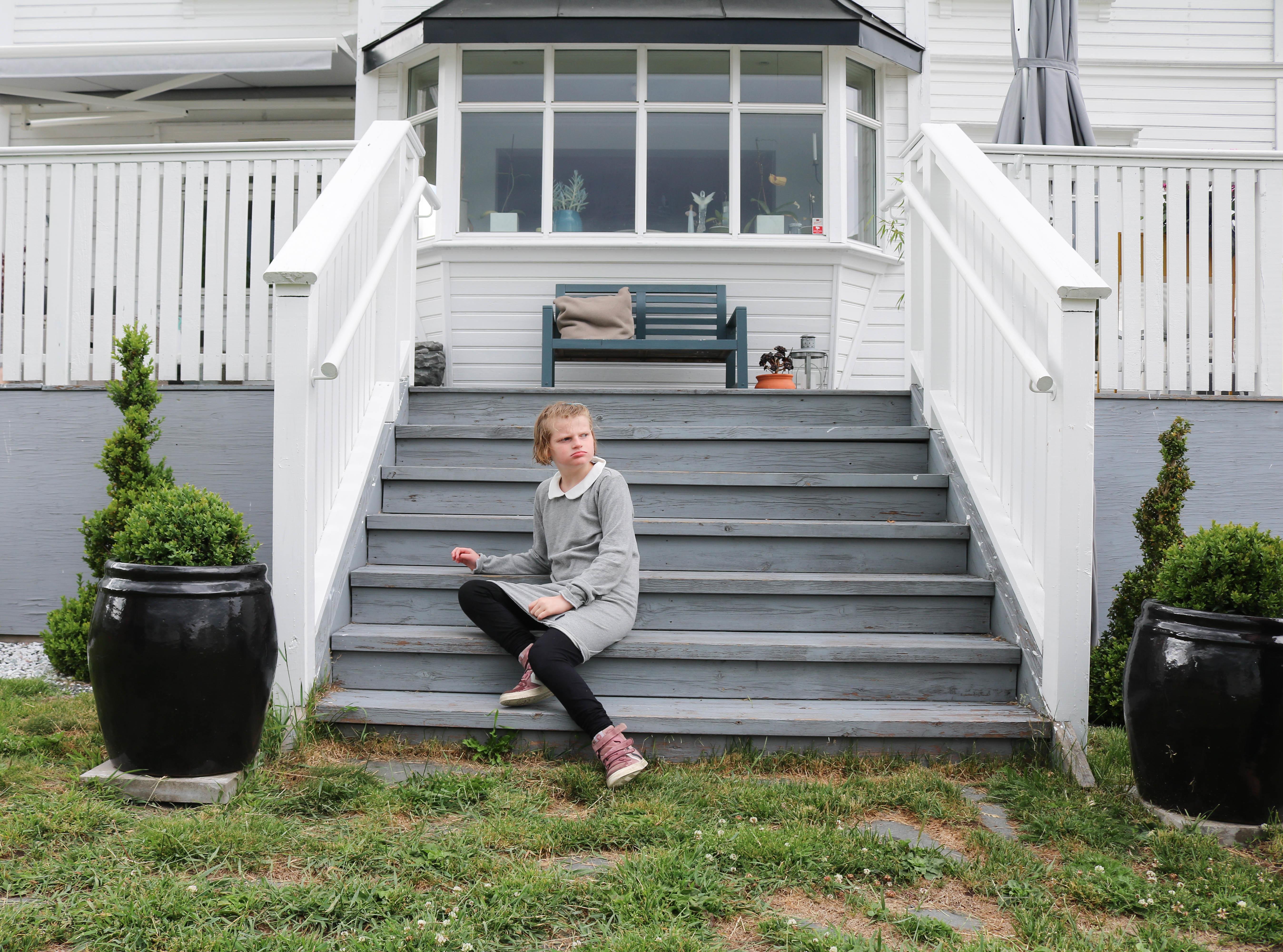 Jente i grå kjole sitter på en grå tretrapp som fører opp til en terrasse og kanapp, tilhørende en hvit trevilla.