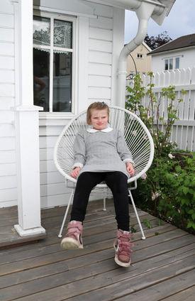 Jente i grå kjole og røde joggesko sitter i en kurvstol på en terrasse.