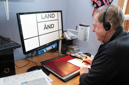 Inne på et hjemmekontor. Eldre mann med headsett løser kryssord på sin datamaskin ved hjelp av et forstørrelsesprogram.