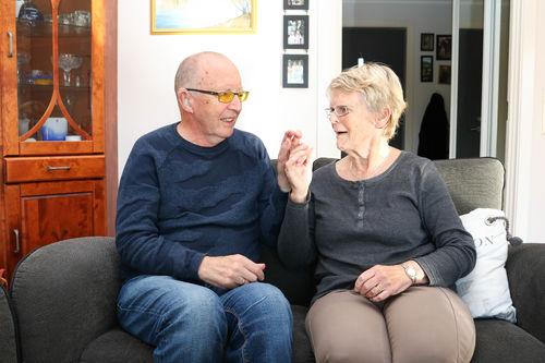 Eldre ektepar sitter tett i en sofa, de kommuniserer med taktilt tegnspråk. Mann til venstre, kvinne til høyre.