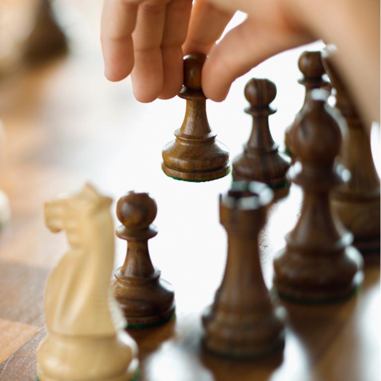 Nærbilde av sjakkbrett og en hånd som løfter en av brikkene