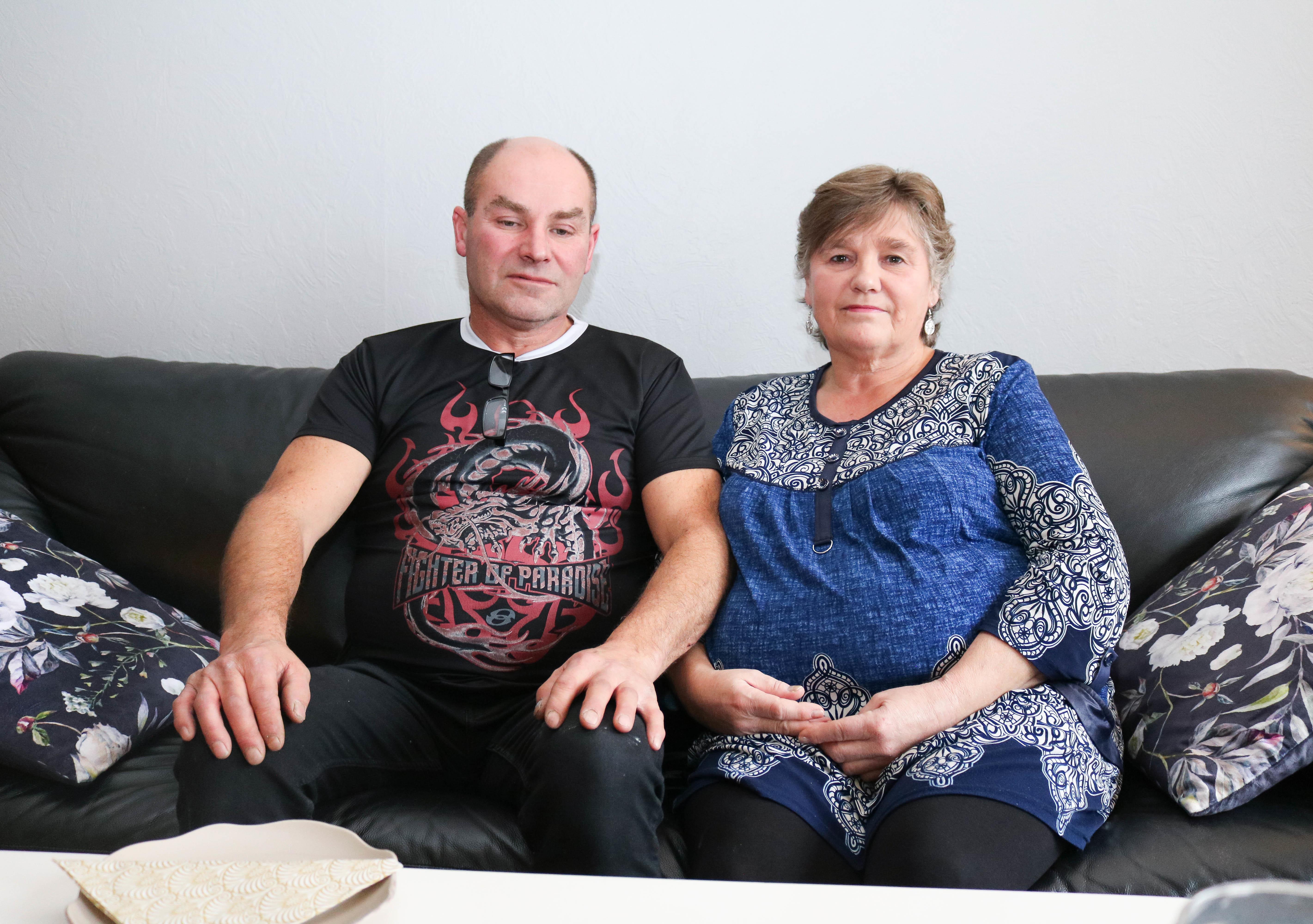 Ektepar, han i svart t-skjort og hun i blå skjorte, sitter sammen i grå skinnsofa.