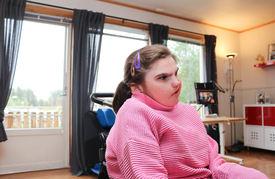 Jeg med CHARGE syndrom sitter i rullestol i sin egen stue. Hun er medfødt døvblind.