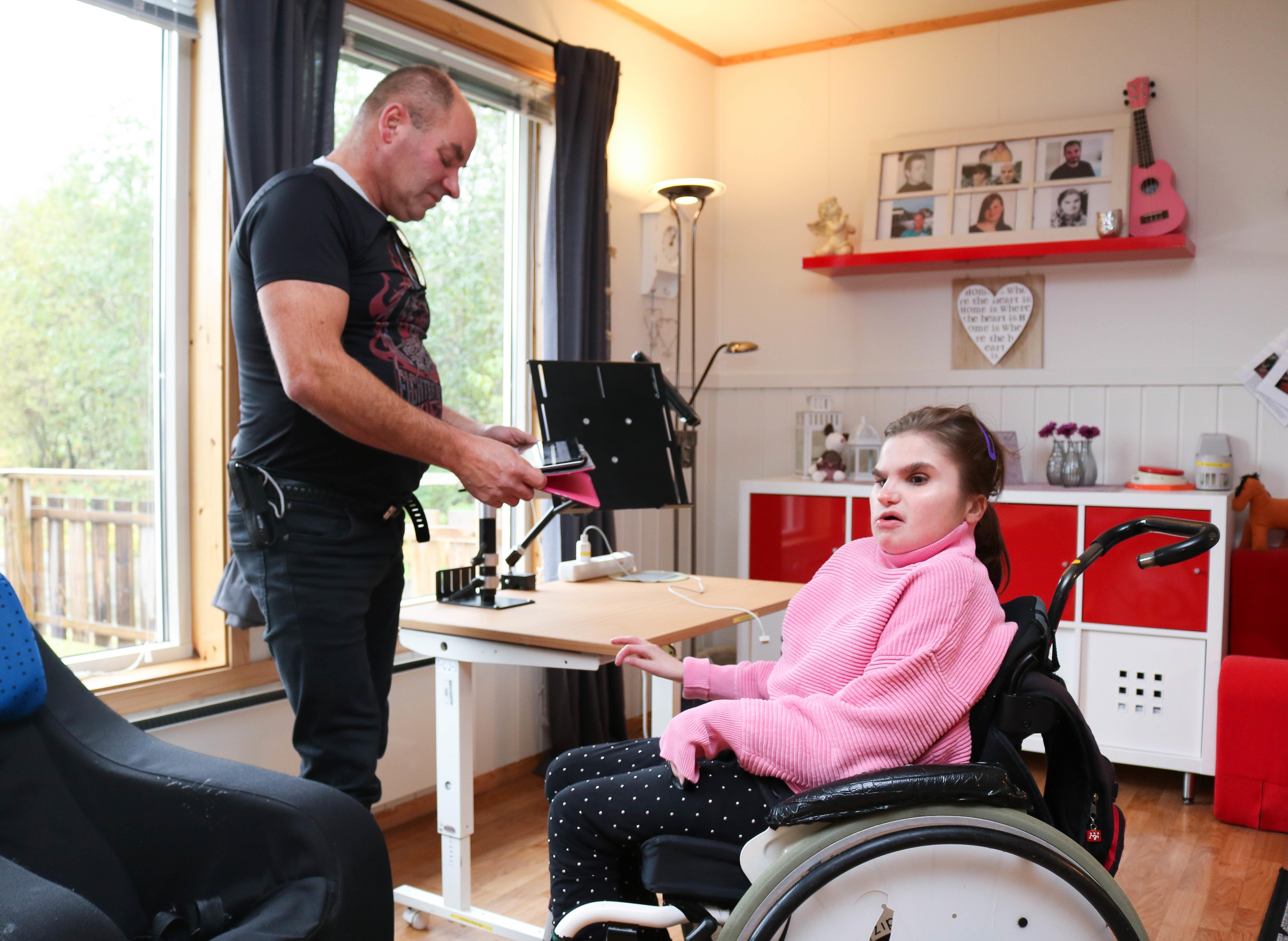 Far hjelper datter i rullestol med hennes Ipad.