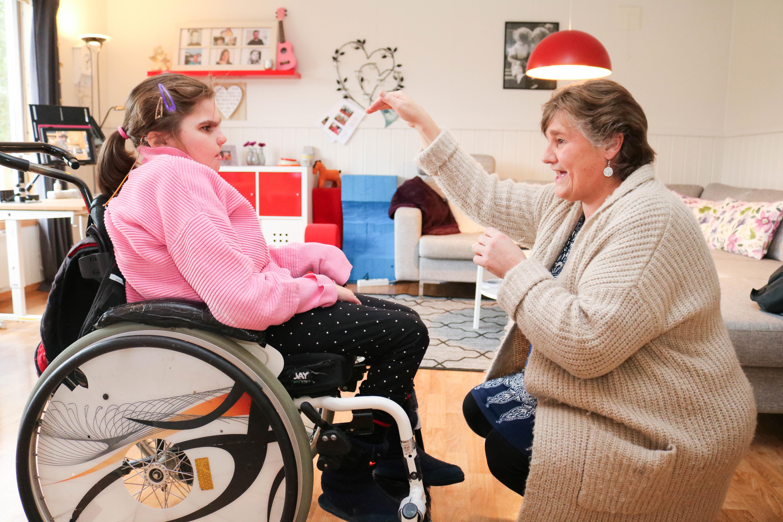 Kvinne kommuniserer ved tegnspråk sammen med sin datter, som sitter i rullestol