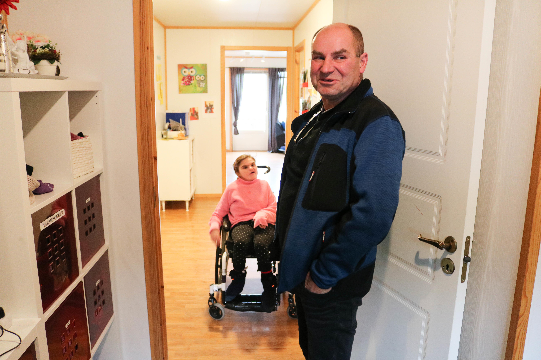 Mann står oppreist i yttergang og ser på kamera, mens hans datter i rullestol er på vei inn i gangen fra stua si.