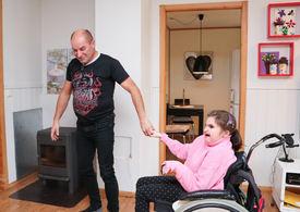 Mann ledsager sin datter i rullestol gjennom stue.