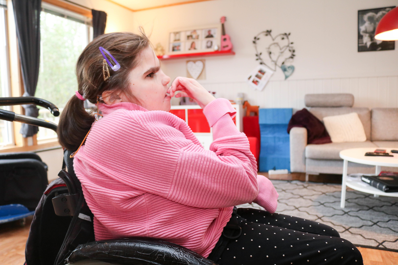 Jente med CHARGE syndrom sitter i rullestol i sin egen stue. Hun holder høyre hånd mot munnen sin.