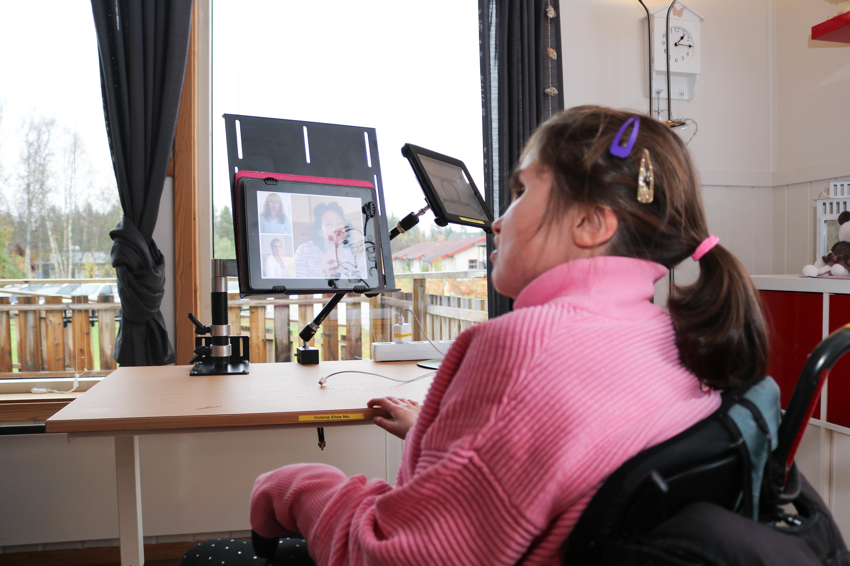 Jente med CHARGE syndrom sitter foran Ipadden sin, som er festet til et stativ på et bord.