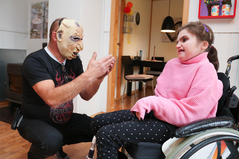 Mann med skummel maske sitter på huk, og kommuniserer ved tegnspråk sammen med sin datter, som har CHARGE syndrom og sitter i rullestol.