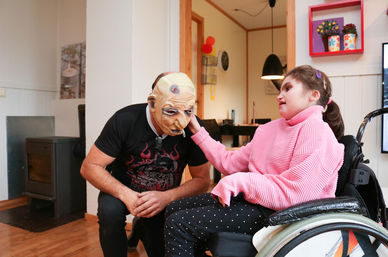 Mann med skummel maske sitter på huk, mens hans datter i rullestol kjenner på masken.