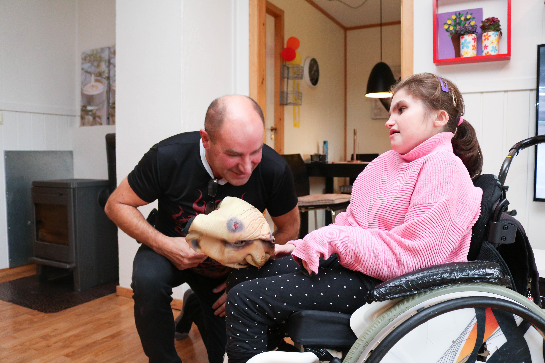 Mann sitter på huk ved sin datter i rullestol, som akkurat har dratt av ham en skummel maske.