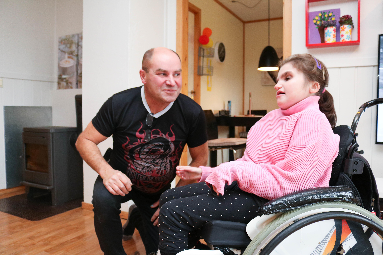 Mann sitter på huk og ser på sin datter, som sitter i rullestol og har på seg rosa genser.