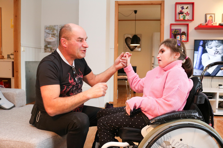 Far kommuniserer med tegnspråk sammen med sin datter. Hun sitter i rullestol og de er hjemme i hennes egen stue.