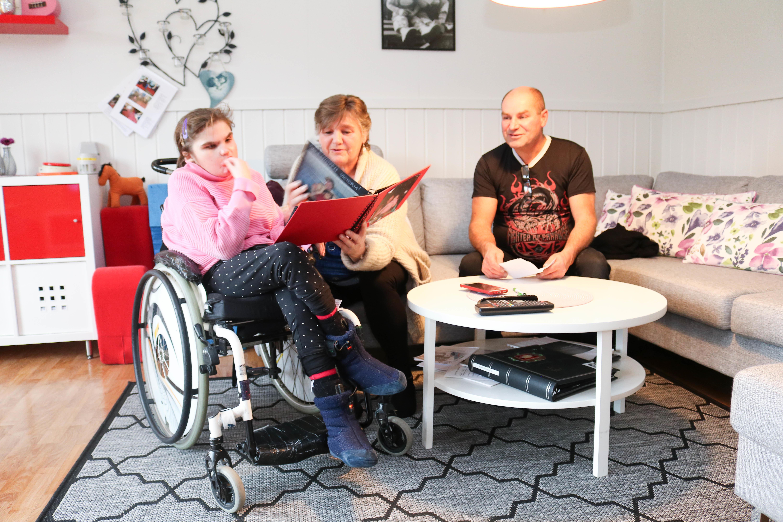 Jente i rullestol har besøk av sine foreldre. De sitter sammen rundt et stuebord og blar i gjennom et rødt fotoalbum.