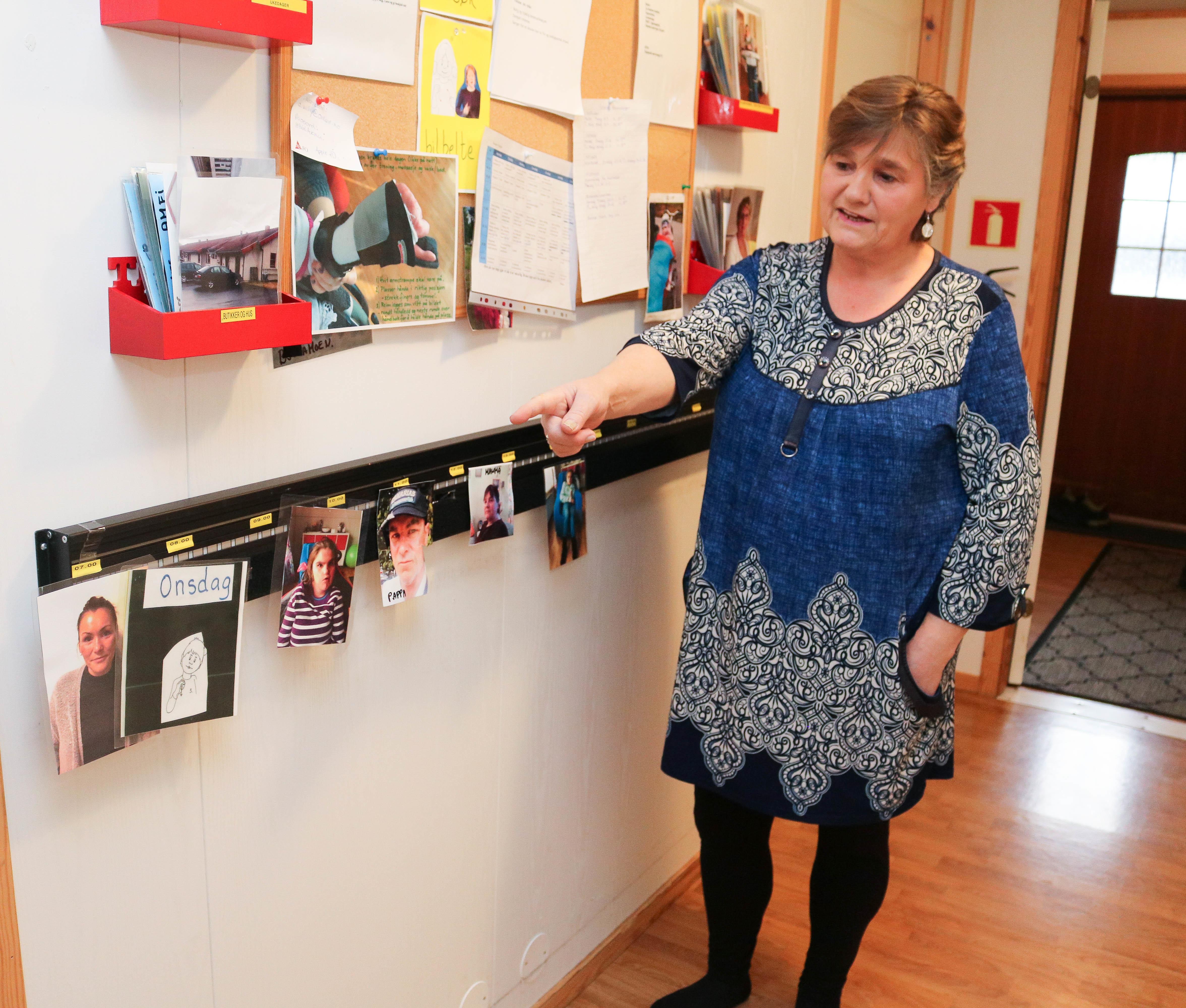 Kvinne i blå kjole viser fram en foto-list som henger i en gang. En korktavle med en rekke papirer henger over listen.