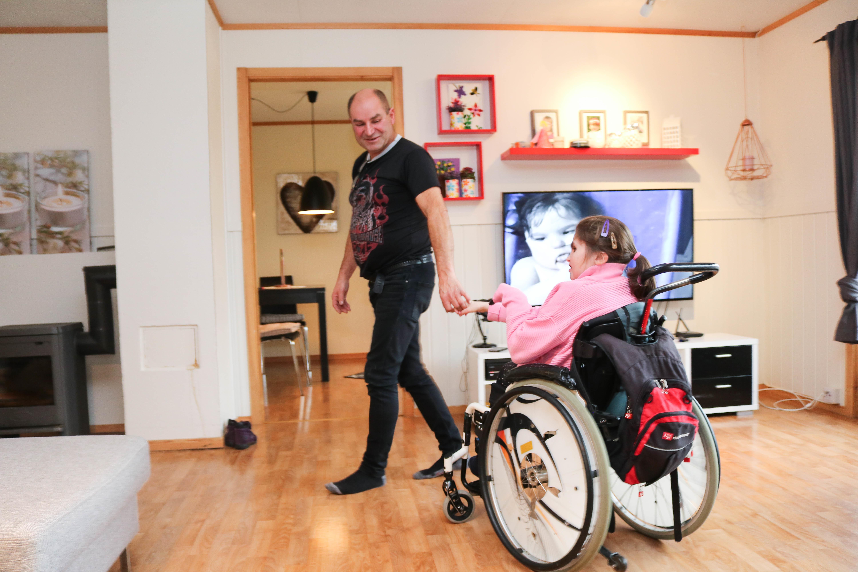 Mann geleider sin datter i rullestol, gjennom hennes egen stue. Tven hennes står på i bakgrunnen.