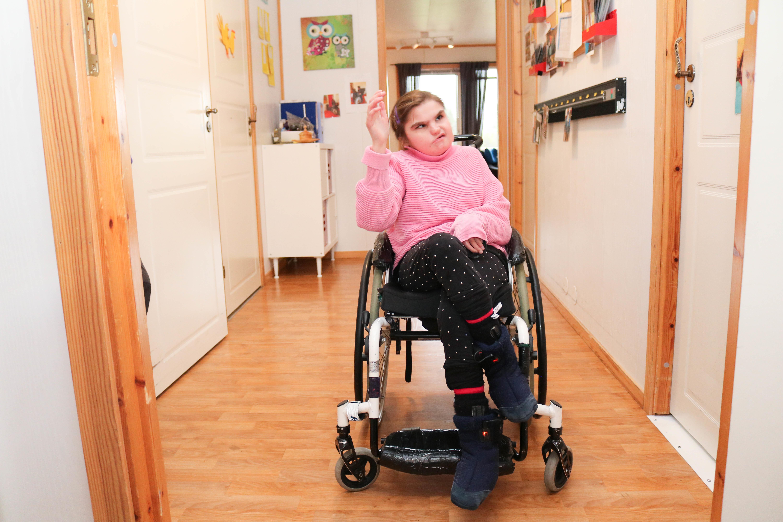 Jente sitter i rullestol i sin egen leilighet, hun vinker til kamera.