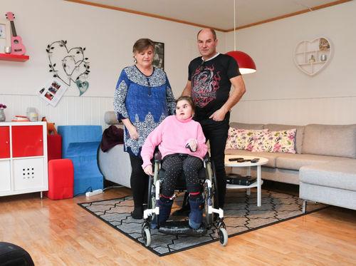 Mor og far står bak deres datter i rullestol, hun har CHARGE syndrom og de er i hennes egen stue.