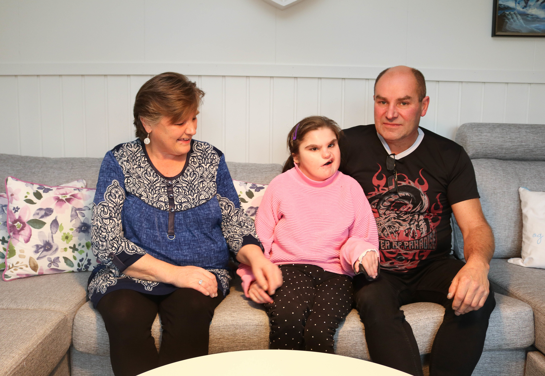 Datter sitter mellom mor og far i en sofa.