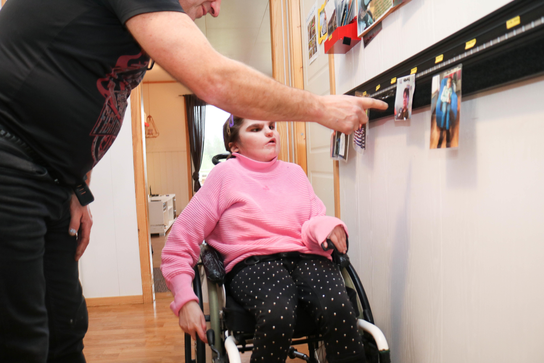 Far peker på et foto på en bildelist, mens datter i rullestol ser på.