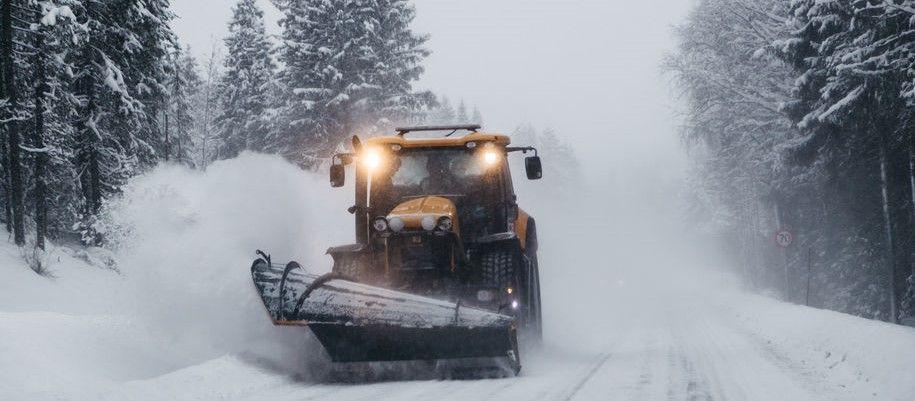 Bilde av traktor med sjær som brøyter snø