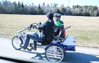 To personer sykler på en horisontandelt tandemsykkel i landlige omgivelser.