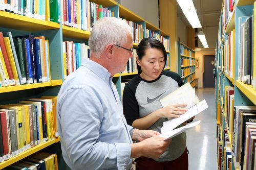 Døvblind mann blar i en bok, sammen med en kvinnelig ledsager, mellom en rekke med gule bokreoler, inne på et bibliotek.