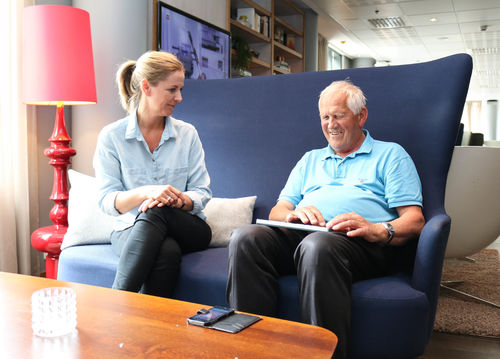 Eldre døvblind mann sitter i en blå sofa med sin ipad. En kvinnelig tolk/ledsager sitter til venstre for ham.