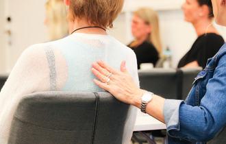 Tolk/ledsager i blå skjorte berører ryggen til døvblind kvinne med haptisk tegnspråk.