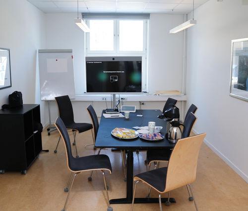 Møterom med plass til cirka åtte personer. Frukt, kaffe og lefser står fremme på møtebordet.