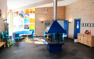 Fellesrom på skole med åpen peis midt i rommet, sollys strømmer inn fra stort, fargerikt hjørnevindu til venstre i rommet.