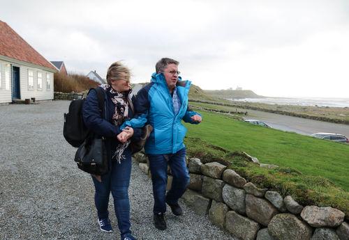 Kvinne ledsager mann med CHARGE-syndrom ved et steingjerde, utenfor Hå gamle prestegård på Jæren.