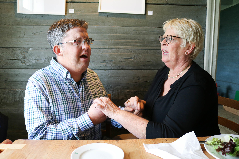 Tolkesituasjon: Mann med CHARGE-syndrom tolkes taktilt av kvinne med lyst hår og briller. De sitter ved et kafebord, i bakgrunnen en grønn trevegg.
