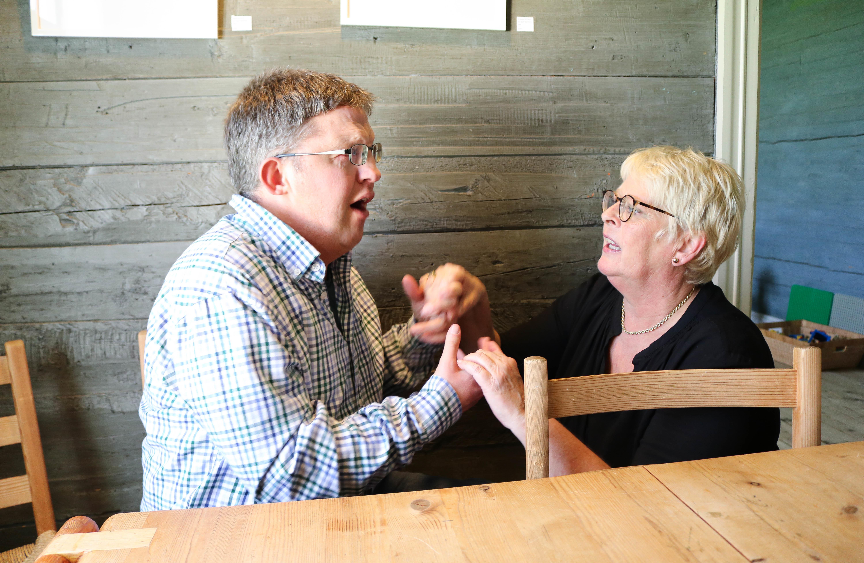 Tolkesituasjon: Mann med CHARGE-syndrom tolkes taktilt av kvinne med lyst hår og briller. Dette foregår ved et kafebord, i bakgrunnen en grønn trevegg.