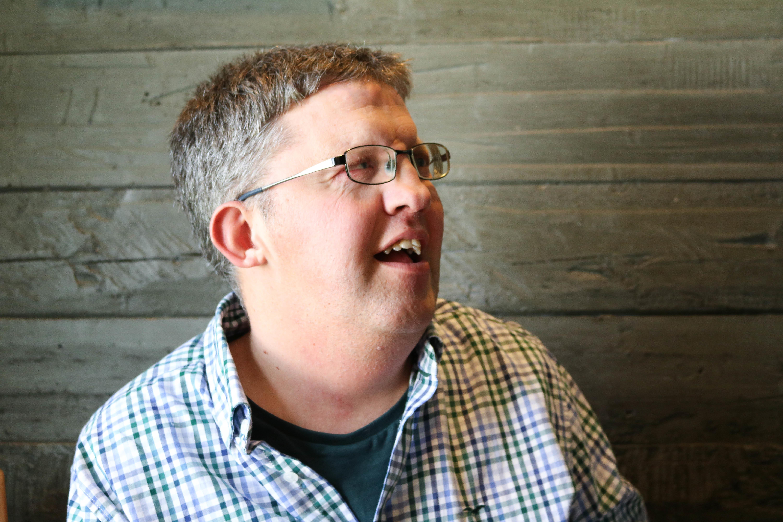 Nærbilde av mann med CHARGE-syndrom, han smiler og ser til venstre for seg selv. Grønn trevegg i bakgrunnen.