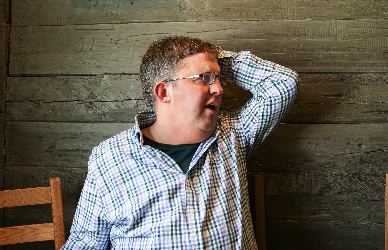 Mann med CHARGE-syndrom er frustrert og holder høyre arm over hodet sitt.