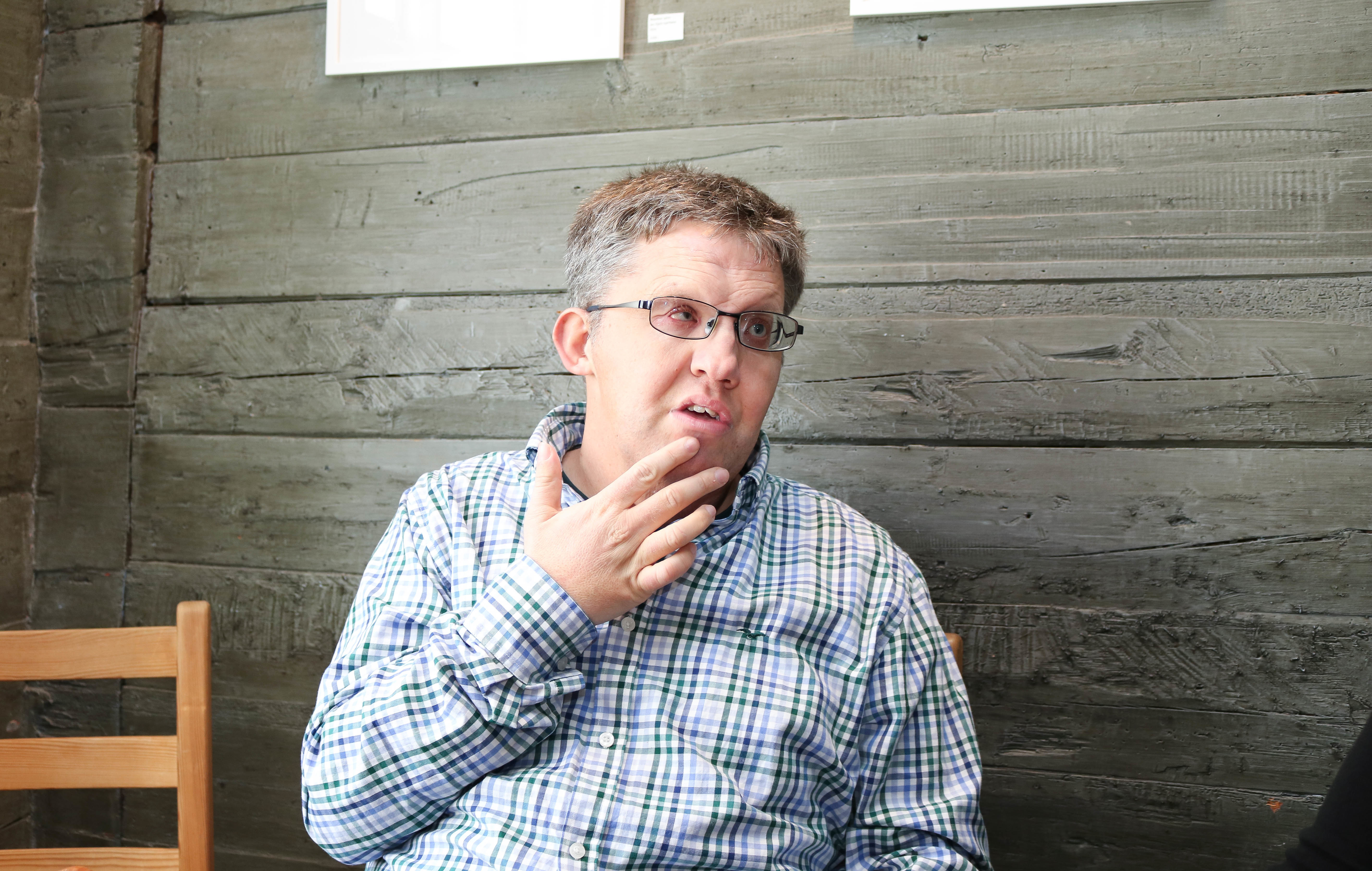 Mann med CHARGE-syndrom har på seg briller og rutete skjorte. Han er i en samtale og holder høyre hånd opp mot munnen.