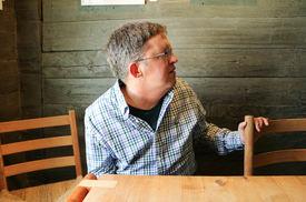 Grønn trevegg i bakgrunnen. Mann med Charge-syndrom sitter mellom to spisestoler av lyst tre.