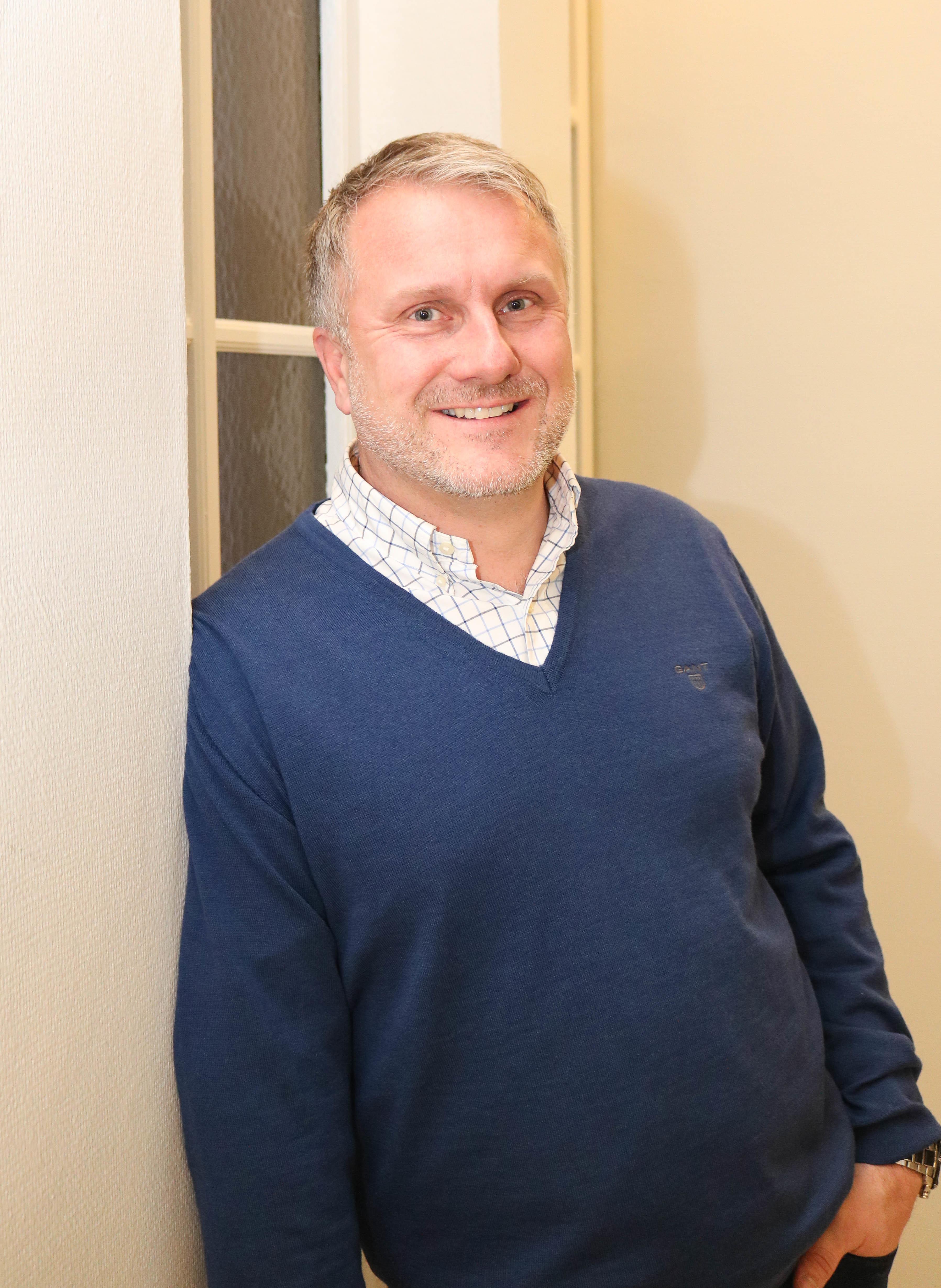 Smilende mann i blå genser lener seg mot en hvit vinduskarm.