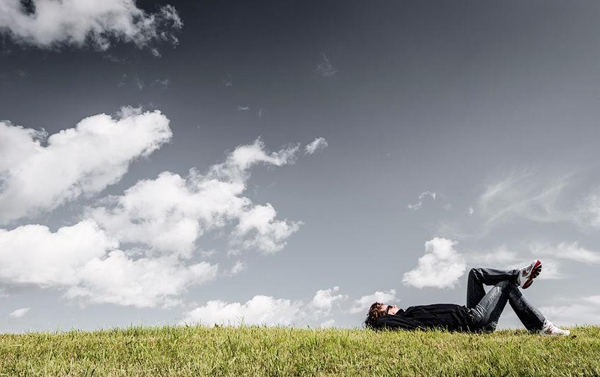 Illustrasjonsfoto fra Pixabay, gutt som ligger på gresset og ser opp i skyene